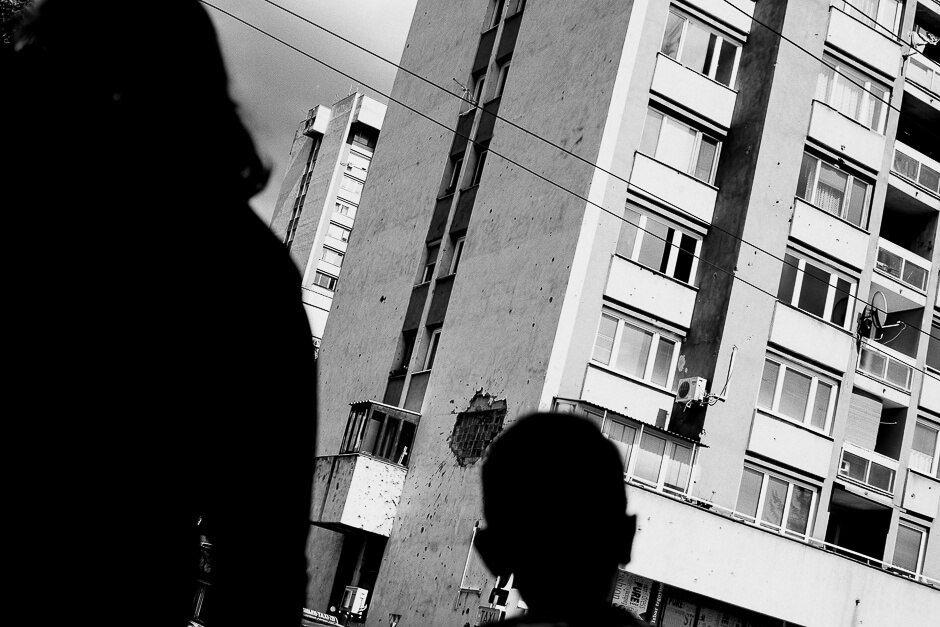Boy looking at a bombshelled house in Sarajevo.