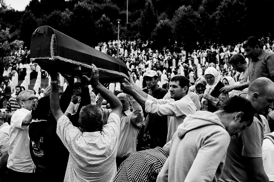 Muslim Bosnians carrying coffins of newly identified victims of genocide to the graves at the Srebrenica Potočari Memorial.
