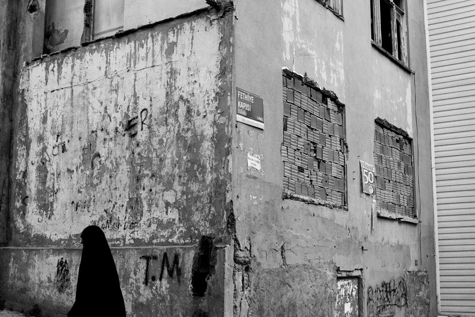 Muslim woman walking past a wall in the Balat neighborhood - Istanbul/Turkey