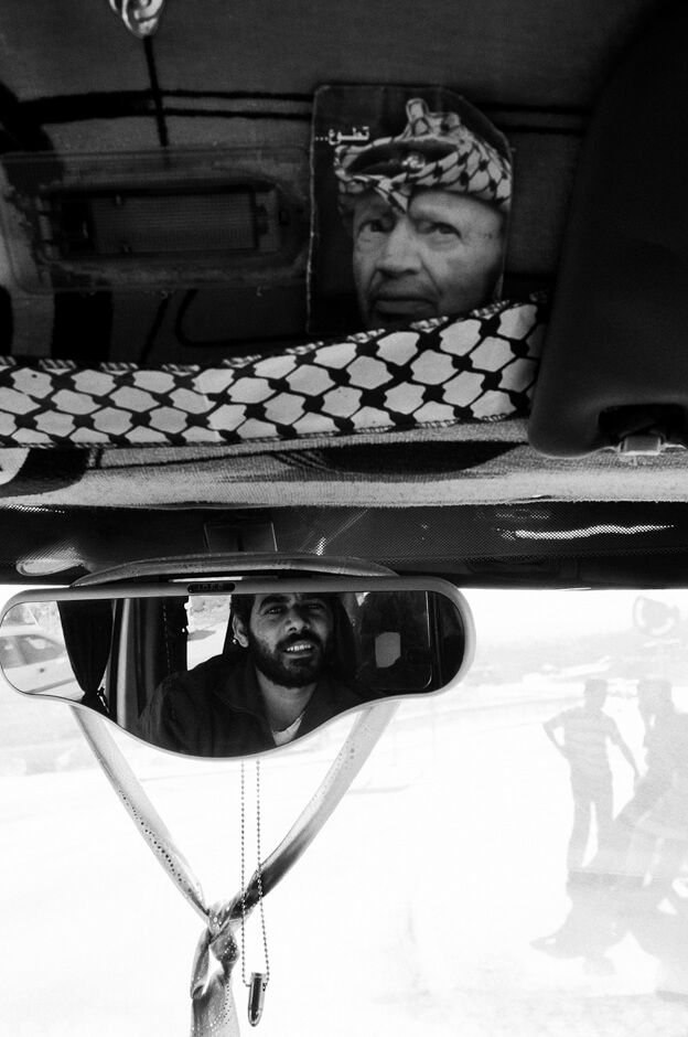 Inside a Palestinian taxi with Jassir Arafat and a bullet close to Bethlehem/West Bank.