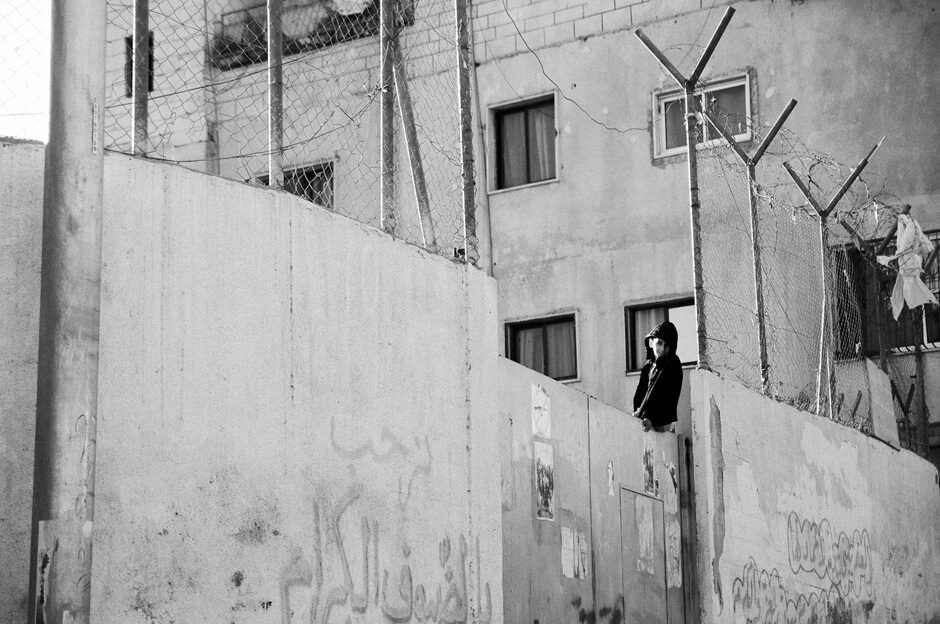 Palestinian boy sitting on a wall in a refugee camp in Bethlehem.