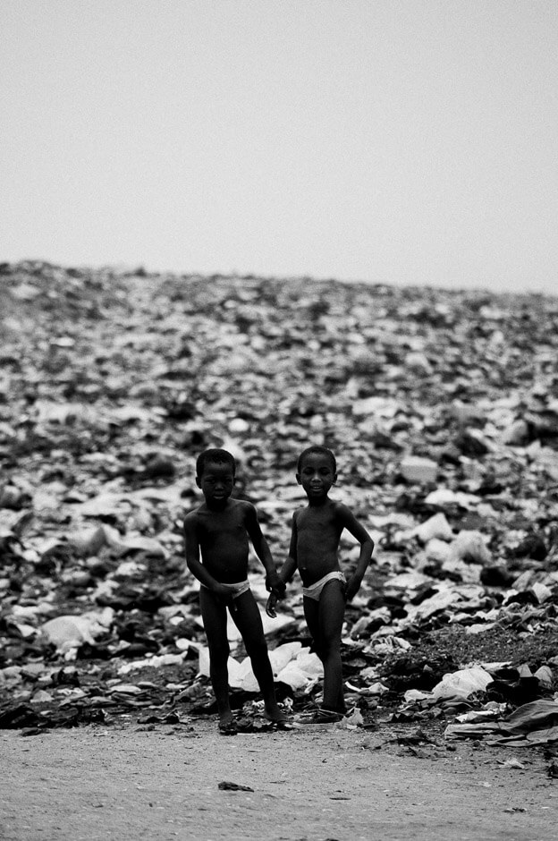 Two boys surrounded by trash in the neighbourhood of Agbogbloshie in Ghanas capital Accra, better known by the locals as Sodom & Gomorrah.