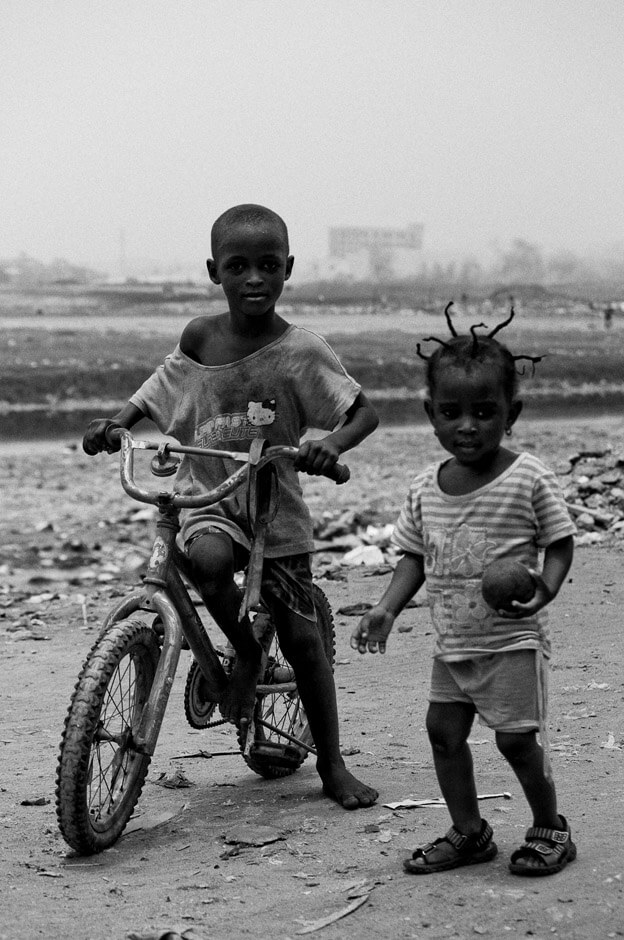 Two children surrounded by trash in the neighbourhood of Agbogbloshie in Ghanas capital Accra, better known by the locals as Sodom & Gomorrah.