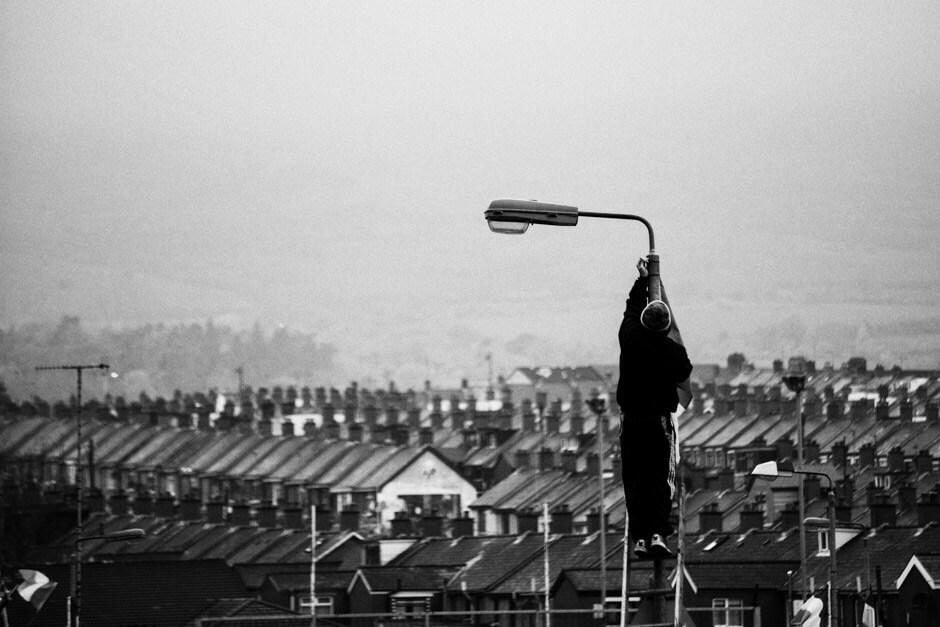 Irish national flag being hoisted over Ardoyne/Belfast for easter rising commemorations.