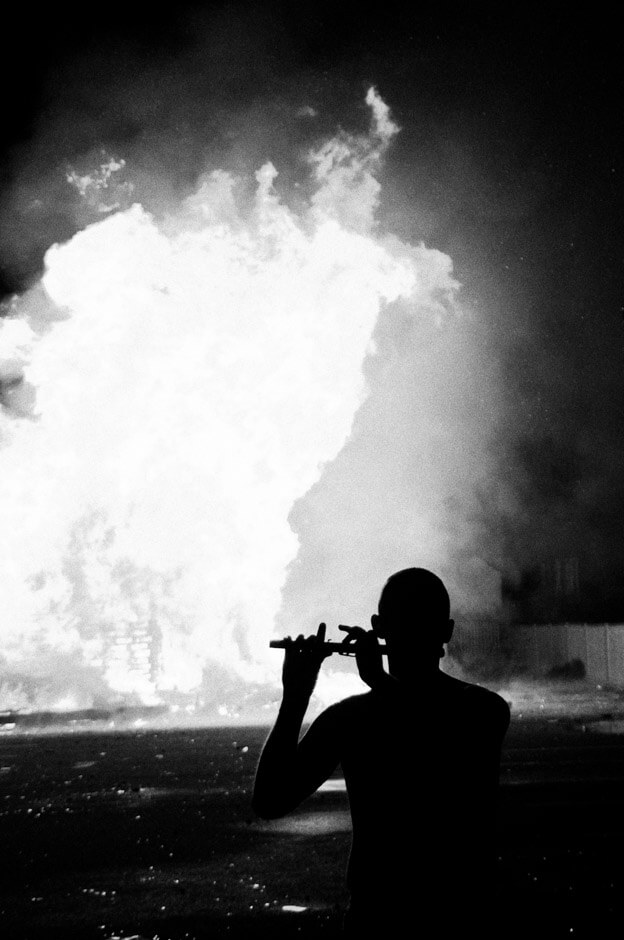 Bandsman playing the flute at the bonfire on the 11th night in Sandy Row/Belfast.